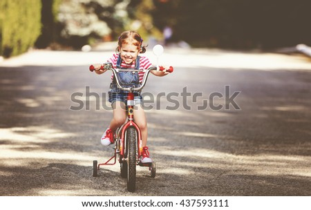 happy child girl cyclist riding a bike on the road - stock photo