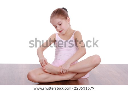 Happy child girl doing gymnastic exercises on the floor - stock photo