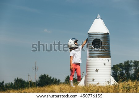 Happy child girl dressed in an astronaut costume playing with hand made rocket. Summer outdoor - stock photo