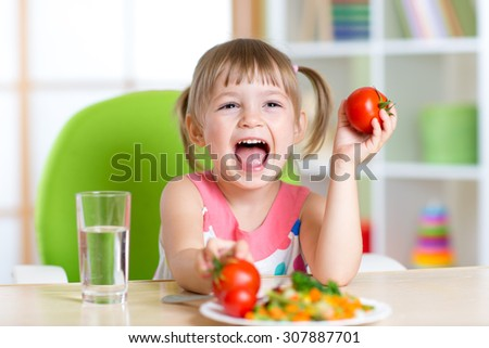 happy child girl eats dinner and shows tomatoes