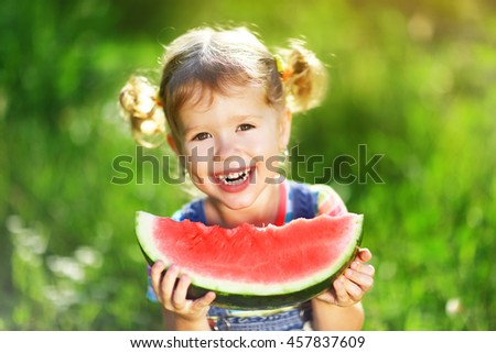 Happy child girl eats watermelon in the summer