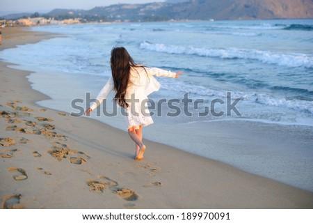 Happy child girl enjoying her beach vacation - stock photo