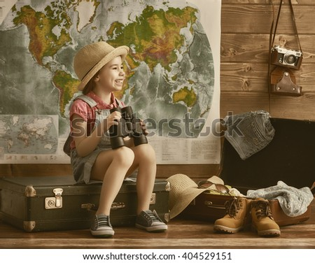 Happy child girl getting ready for the journey. Girl packs her bags and having fun. - stock photo