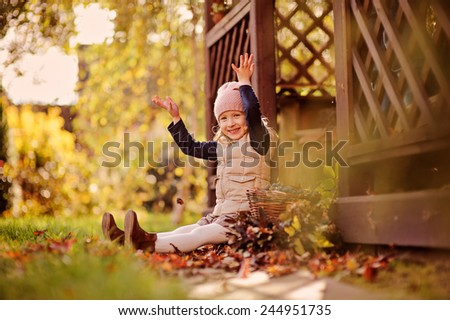 happy child girl having fun and playing with leaves in sunny autumn garden, sitting at wooden house - stock photo