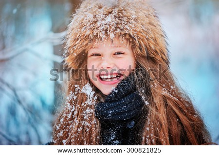 happy child girl head shot on the walk in winter snowy forest in fur hat