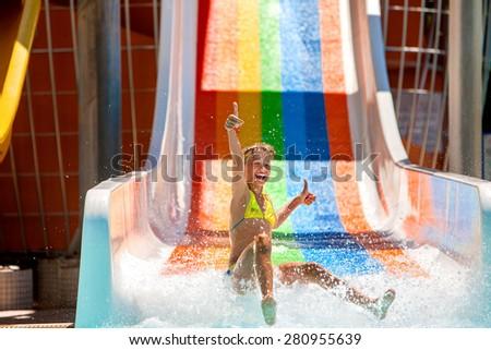 Happy child girl in bikini showing thumb up sliding water park. - stock photo