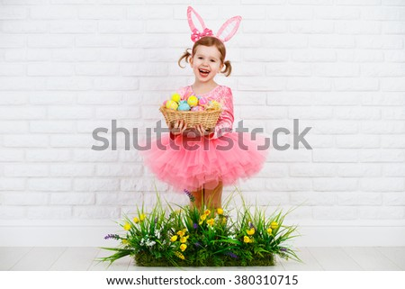 Happy child girl in costume Easter bunny rabbit with ears and a basket of eggs and green grass with flowers - stock photo