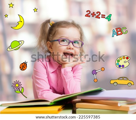 Happy child girl in glasses reading books in library - stock photo