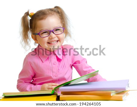 Happy child girl in glasses reading books sitting at table - stock photo