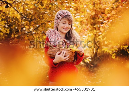 happy child girl in knitted scarf and sweater with basket on autumn walk in forest eating apples. Fall harvest, cozy mood.