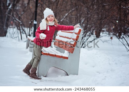 happy child girl in red coat making snowball at wooden bench - stock photo