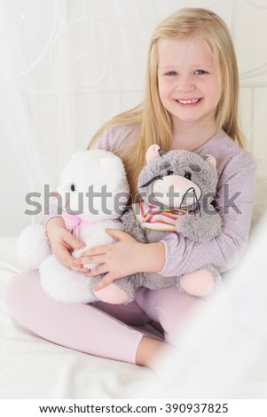 Happy child girl in the bed with her soft toys - stock photo