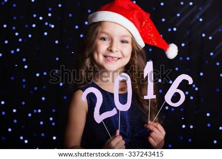 Happy child girl is wearing red santa hat holding numbers 2016 in hands in a studio over background scene with blue lights for a holiday concept. - stock photo