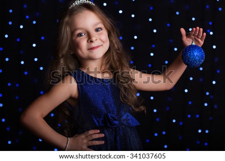 Happy child girl is with blue Christmas tree toy in hands over background scene with lights for a holiday concept. - stock photo