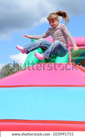 Happy child girl jumps on the inflatable playground - stock photo