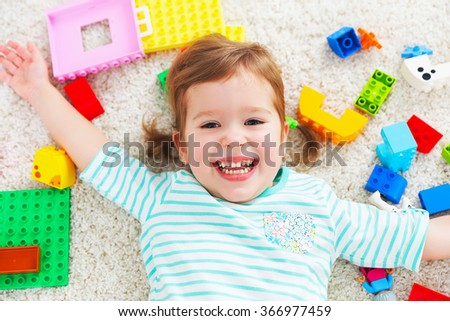 happy child girl laughing and playing with toys constructor - stock photo