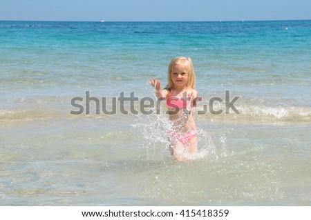 happy child girl on a tropical beach ocean has a fun with splash. Summer vacation concept - stock photo