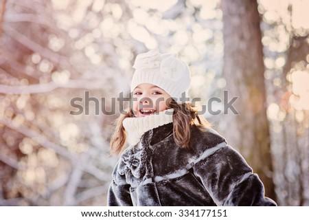 happy child girl on cozy warm outdoor winter walk, outdoor activities on vacation - stock photo