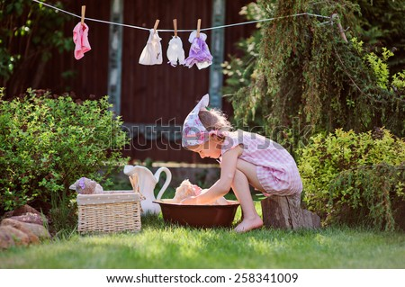 happy child girl playing toy wash in summer garden - stock photo