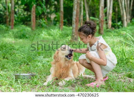 Happy child girl playing with dog golden retriever in green field
