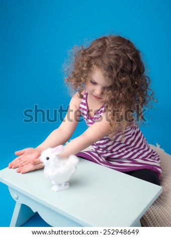 Happy child, girl, playing with easter bunny, looking at camera - stock photo