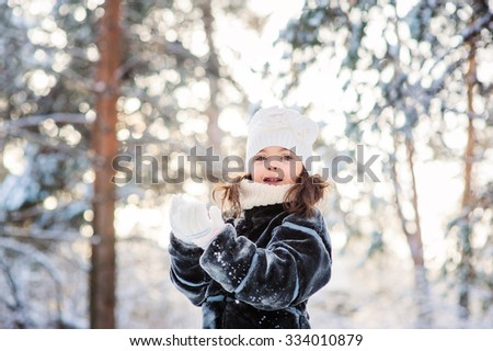 happy child girl playing with snow on the walk in winter forest. Outdoor activity on winter holidays. - stock photo