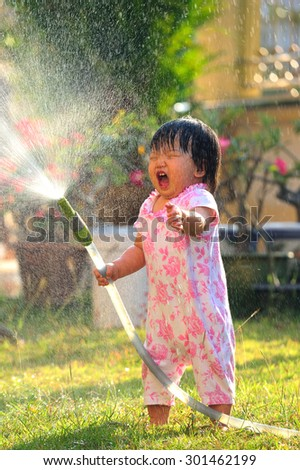 Happy child girl pours water from a house in summer season - stock photo