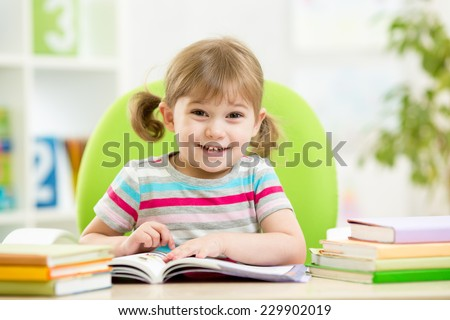 Happy child girl reading book at table in nursery - stock photo