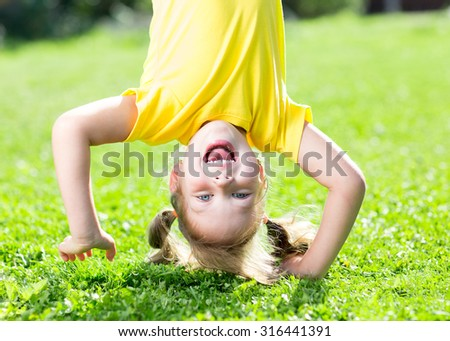 happy child girl standing upside down on her head on grass in summer - stock photo