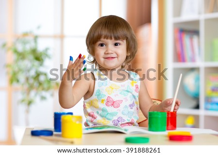 Happy child girl with hand painted color paints - stock photo