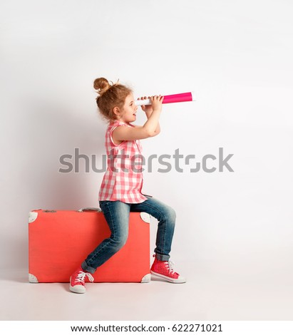 Happy child girl with spyglass, explore and adventure concept