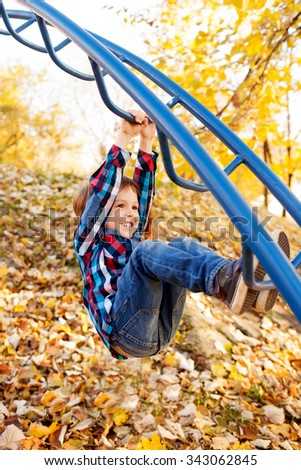 Happy child hanging from a playground cliber, shallow depth of field - stock photo