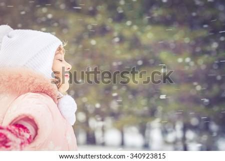 Happy child having fun in winter outdoors - stock photo