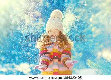 Happy child having fun playing with snow in winter day - stock photo
