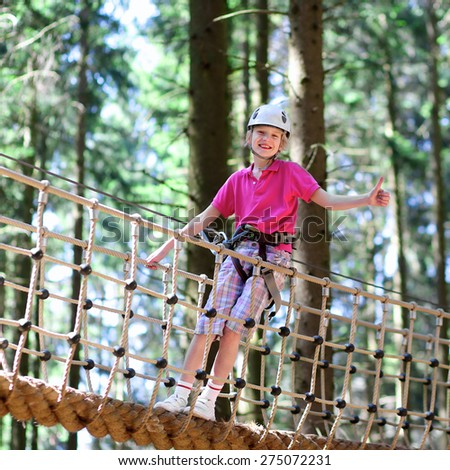 Happy child, healthy teenage school boy enjoying activity in climbing adventure park on a summer day - stock photo