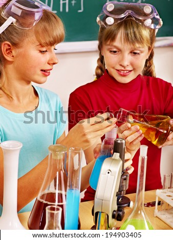 Happy child holding flask in chemistry class. - stock photo