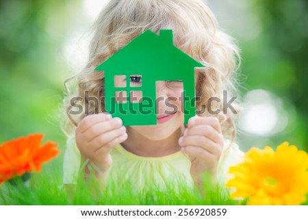 Happy child holding house in hands against spring green background. Real estate business concept - stock photo