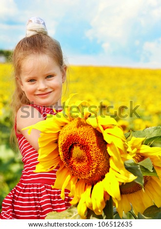 Happy child holding sunflower outdoor.