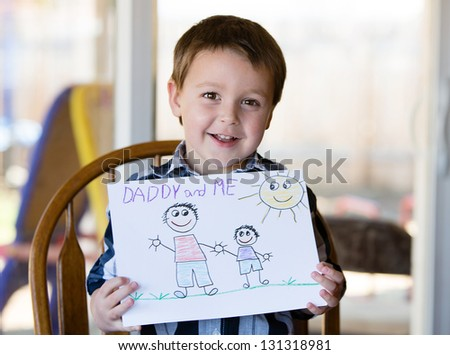 "Happy child holds up a drawing for his Dad; ""I Love Daddy"""