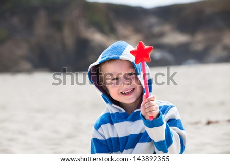 Happy child in a stripy beach cover-up holding a star-wand - stock photo