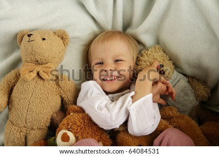 Happy child in bed with teddy bear - stock photo