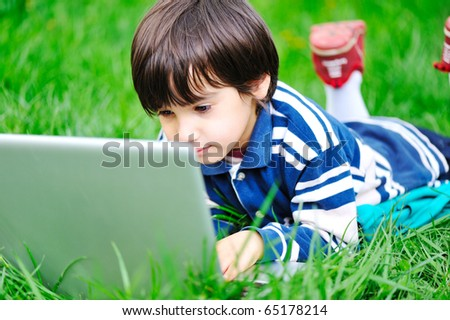 happy child in nature outdoor working and playing on laptop, green grass on ground - stock photo