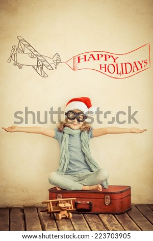 Happy child in Santa Claus hat. Kid playing with toy airplane at home. Retro toned - stock photo