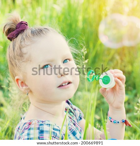 Happy Child in Summer.  Beautiful Girl Blows Soap Bubbles Outdoor. Happy Children. Healthy Kids. Spring Time. - stock photo