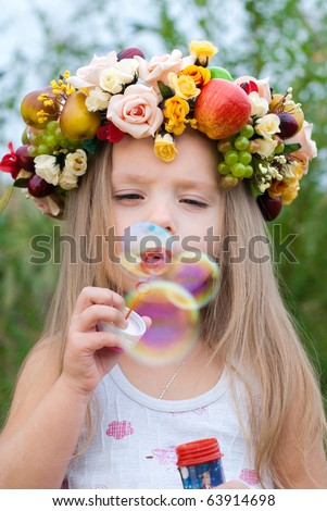 Happy Child in Summer.  Beautiful Girl with Flowers Wreath from Flowers blows Soap Bubbles. Happy Children. Healthy Kids. Spring Time. - stock photo