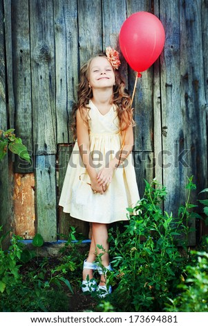 Happy Child in Summer.  Beautiful Girl with Red Balloon in the Garden. Happy Children. Healthy Kids. Spring Time. Vacation in the Countryside.  - stock photo