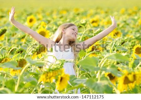 Happy child in sunflowers - stock photo