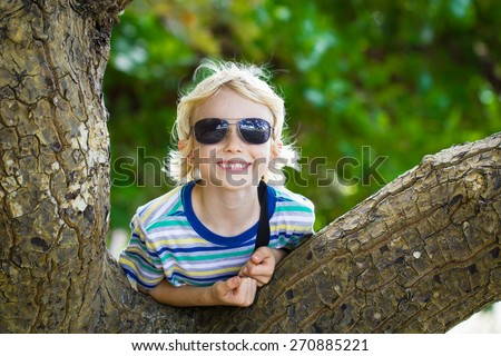 Happy child in sunglasses leaning over tree next to beach - stock photo