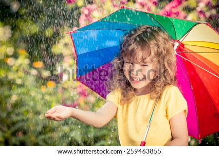 Happy child in the rain. Funny kid playing outdoors in spring park - stock photo