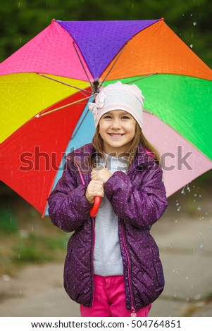 Happy child in the rain. Funny little girl playing outdoors in park.